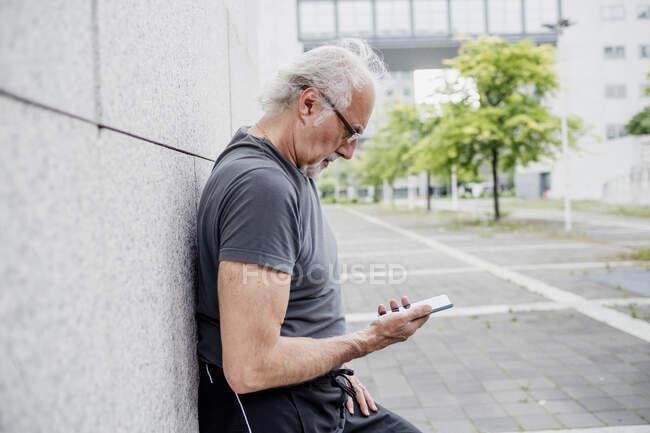 Hombre mayor con anteojos usando teléfono inteligente mientras está parado en la ciudad - foto de stock