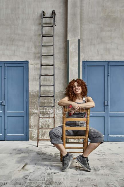 Muratore donna sorridente seduto su sedia di legno contro parete in officina — Foto stock