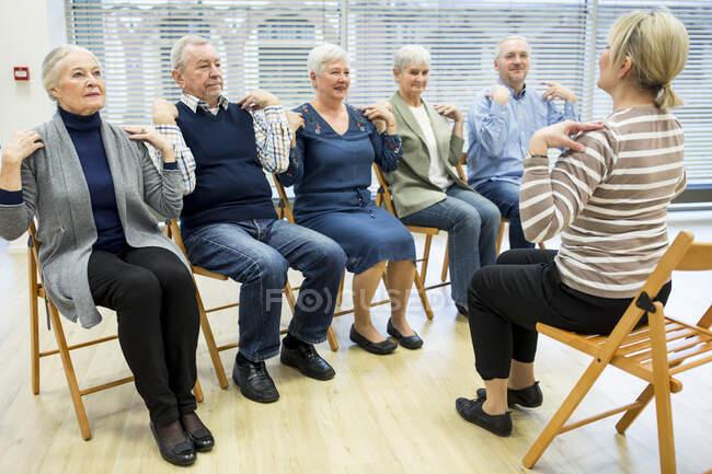 Група старшокласників практикує гімнастику з інструктором на пенсії. — стокове фото