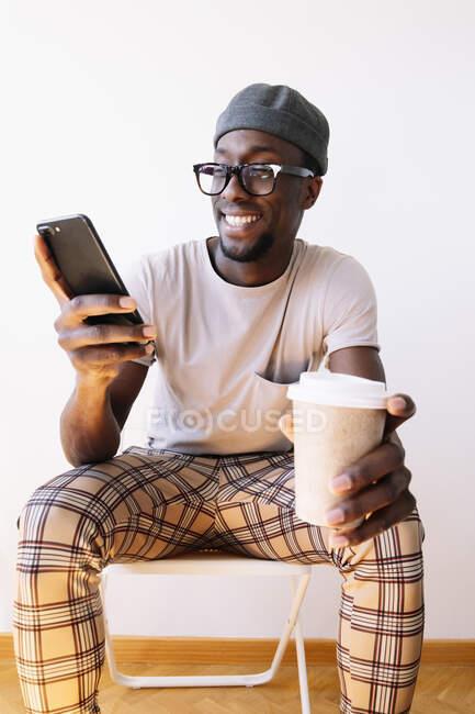 Giovane sorridente utilizzando il telefono cellulare mentre seduto con tazza di caffè contro parete bianca a casa — Foto stock