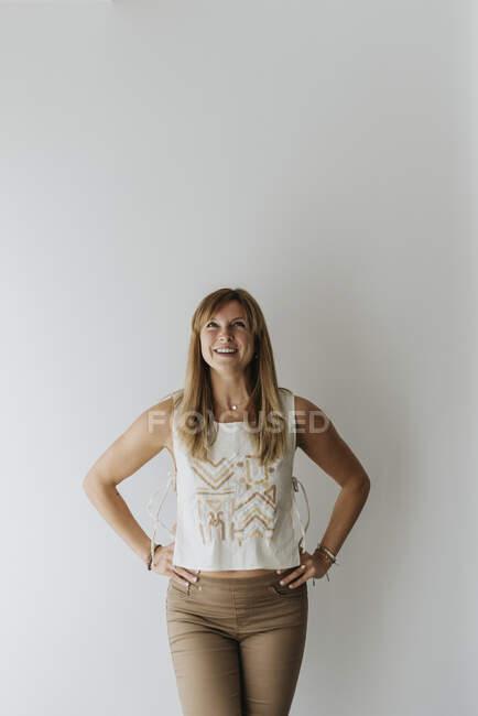 Посмішка красива жінка з руками на стегні дивлячись вгору, стоячи проти стіни вдома. — стокове фото
