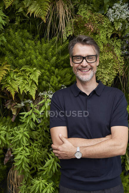 Happy mature man standing arms crossed against plants at yard — Stock Photo