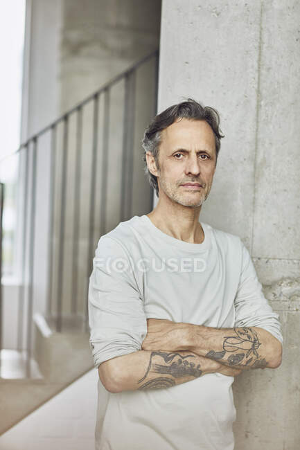 Портрет татуюваного старшого чоловіка на гористій квартирі. — стокове фото