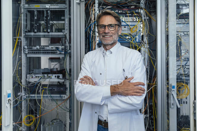 Smiling mature man with arms crossed standing in server room — Stockfoto