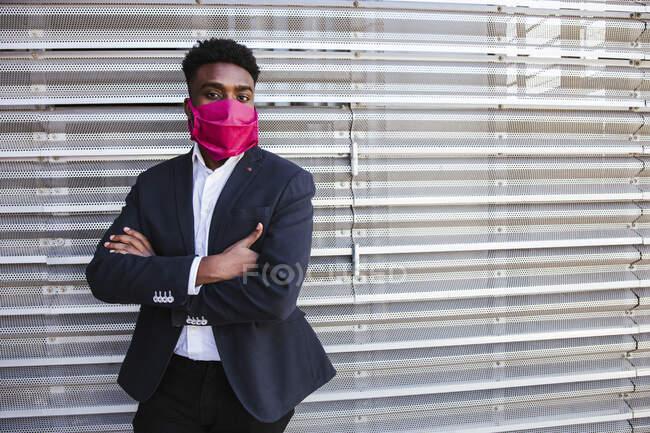 Empresário usando máscara com os braços cruzados de pé contra a parede na cidade — Fotografia de Stock