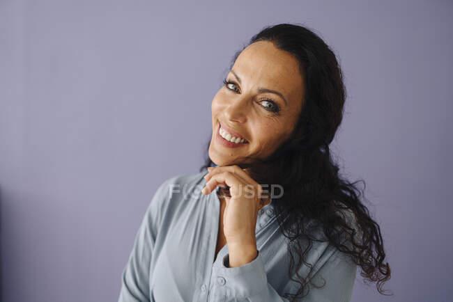 Зблизька щаслива жінка середнього віку з хвилястим волоссям проти фіолетового фону — стокове фото