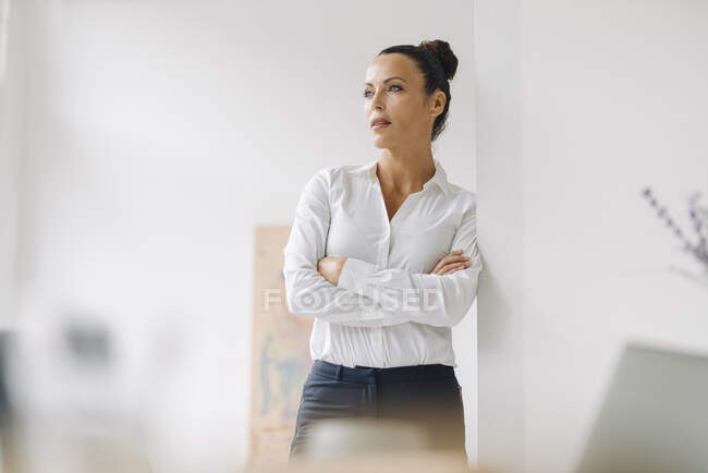 Thoughtful businesswoman with arms crossed standing by wall in home office — Stock Photo