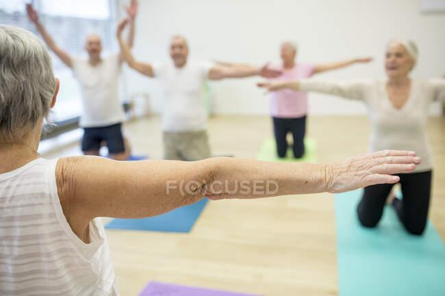 Grupo de personas mayores activas que practican yoga juntas - foto de stock