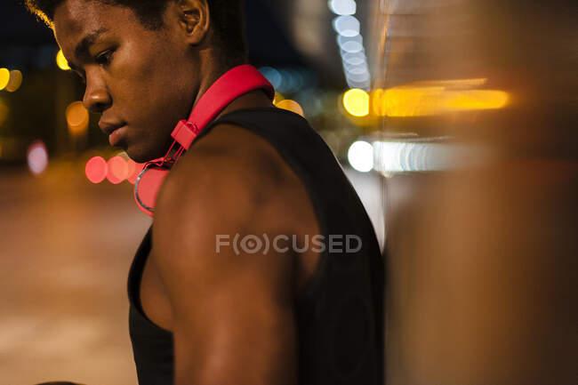 Портрет молодого человека в наушниках ночью с городским освещением — стоковое фото