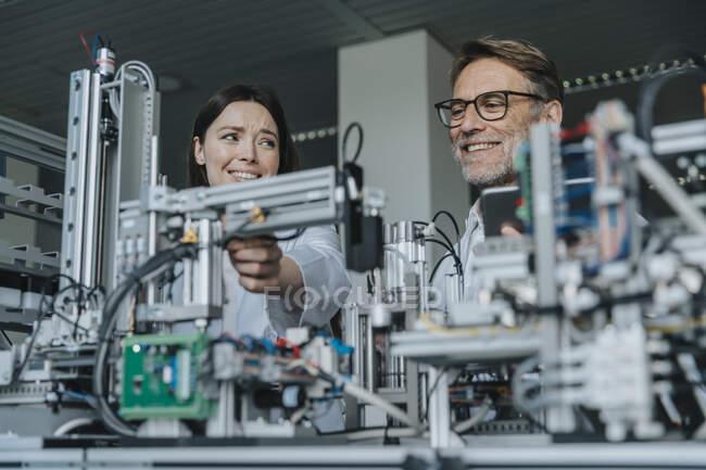 Des ingénieurs souriants, hommes et femmes, examinent des équipements en laboratoire — Photo de stock