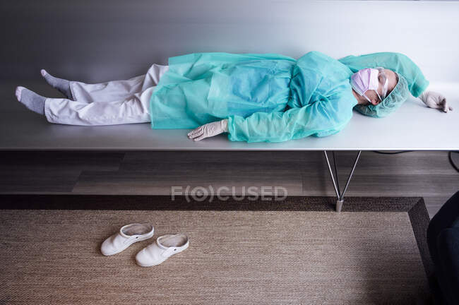 Tired female doctor wearing protective workwear lying on bench in hospital — Photo de stock