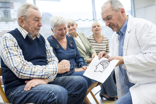 Група похилих віком, що відвідує медичне консультування у відставці з дому. — стокове фото