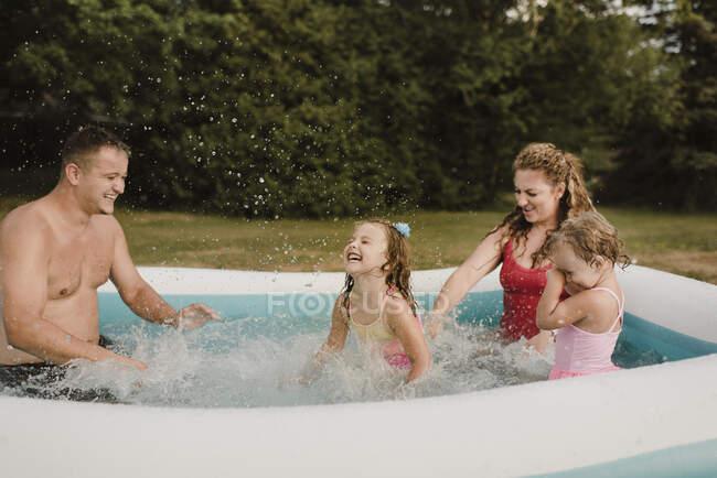 Famiglia felice in una piscina gonfiabile in giardino — Foto stock