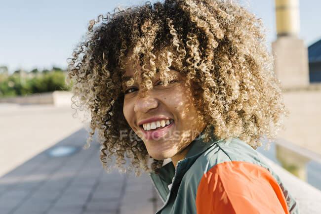 Mujer joven feliz con el pelo rizado durante el día soleado - foto de stock