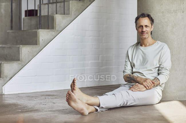 Senior homem sentado no chão em um apartamento loft — Fotografia de Stock