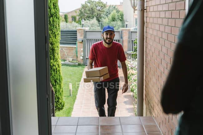 Улыбающийся почтальон доставляет посылки пожилой женщине — стоковое фото