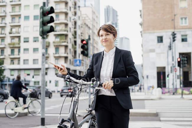 Жіноча професійна музика для слухання під час ходьби на велосипеді по вулицях міста. — стокове фото