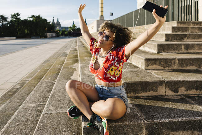 Trendy woman listening music while sitting with arms raised on steps in city — Stock Photo