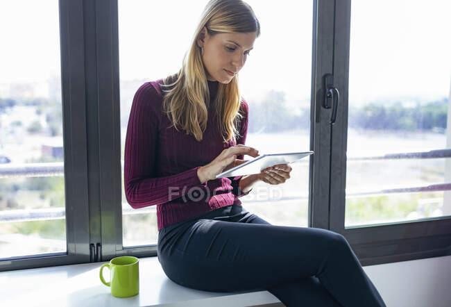 Empresária usando tablet digital enquanto se senta na mesa contra a janela no escritório — Fotografia de Stock