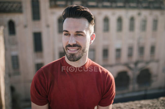 Smiling young man looking away in city — Stock Photo