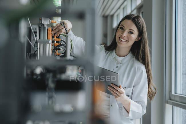 Femme scientifique souriante tenant une tablette numérique inventant des machines en usine — Photo de stock