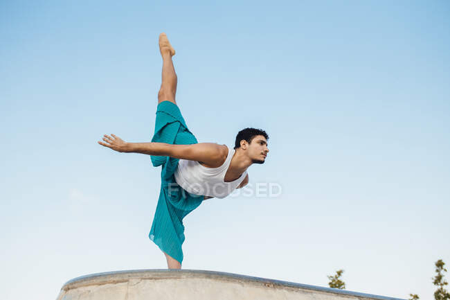 Молодой человек делает гимнастические упражнения на ясном голубом небе — стоковое фото