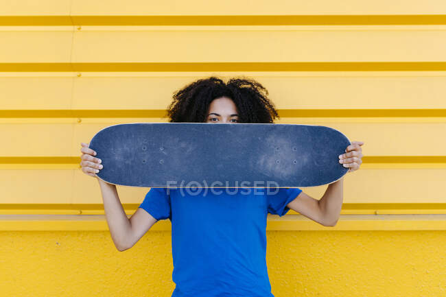 Young woman holding skateboard in front of face, looking at camera — стокове фото