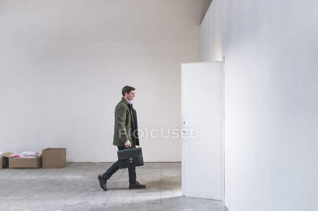 Бізнесмен з портфелем виходить з розрідженої кімнати. — стокове фото