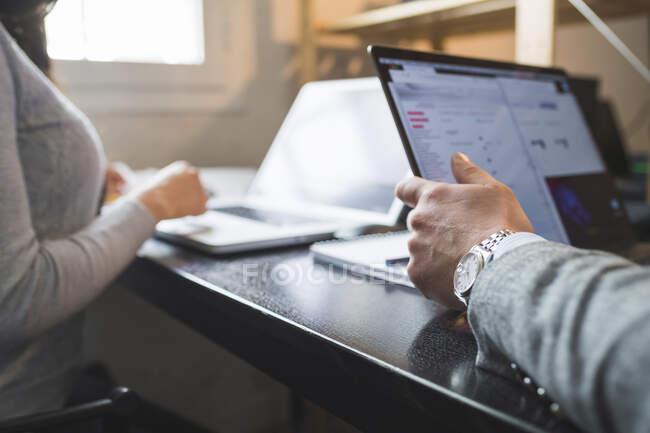 Uomo e donna d'affari che utilizzano computer portatili alla scrivania in ufficio — Foto stock