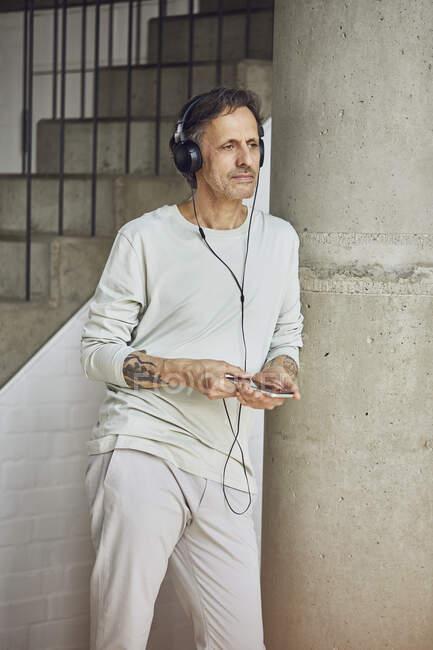 Старший мужчина с наушниками слушает музыку в квартире на чердаке — стоковое фото
