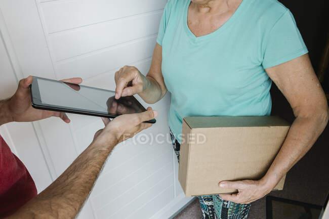 Старшая женщина делает подпись на цифровой табличке, которую держит почтальон в дверях — стоковое фото