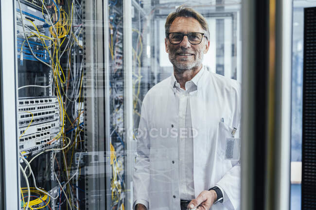 Male IT professional standing by network server in date center seen through glass — Stock Photo