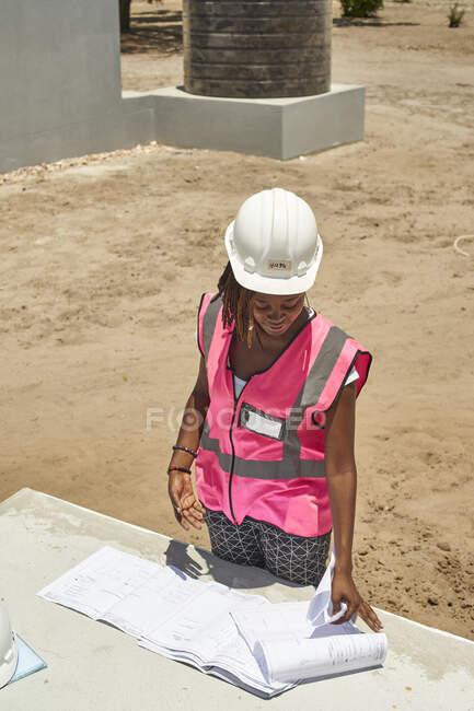 Empreiteira de construção feminina analisando planta na mesa no canteiro de obras — Fotografia de Stock