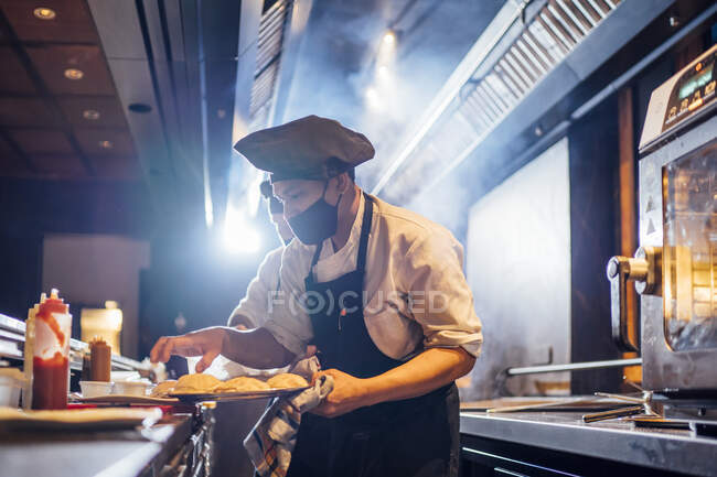 Chef wearing protective face mask preparing a dish in restaurant kitchen — Stock Photo