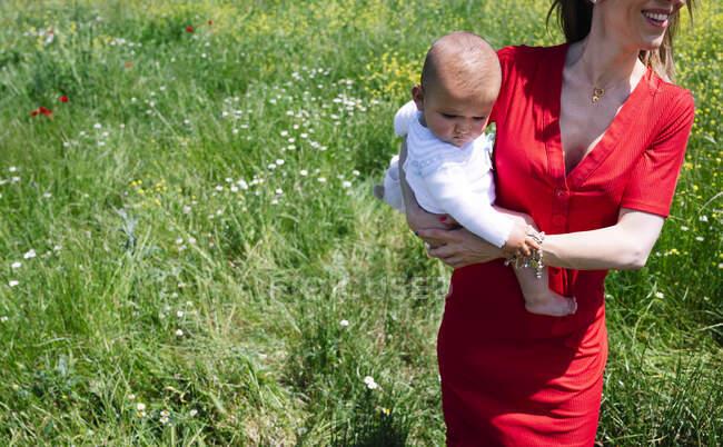 Madre llevando a su hijo bebé mientras está de pie en tierra herbosa durante el día soleado - foto de stock