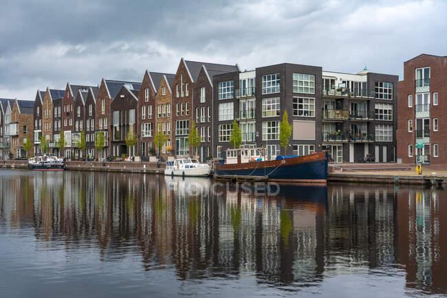 Países Bajos, Holanda del Norte, Haarlem, Casas a lo largo del canal del río Spaarne - foto de stock