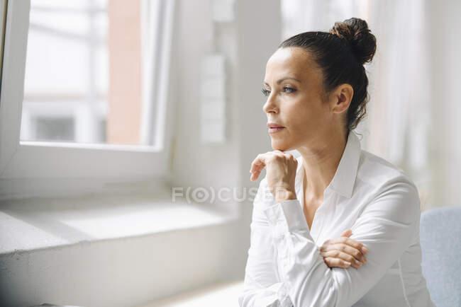 Femme réfléchie professionnelle regardant loin tout en étant assis dans le bureau à la maison — Photo de stock