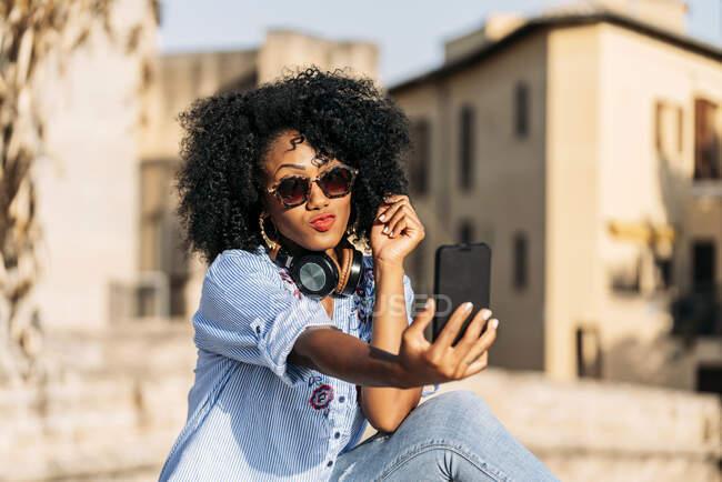 Donna sorridente con capelli afro e occhiali da sole che si fa un selfie con il suo smartphone — Foto stock