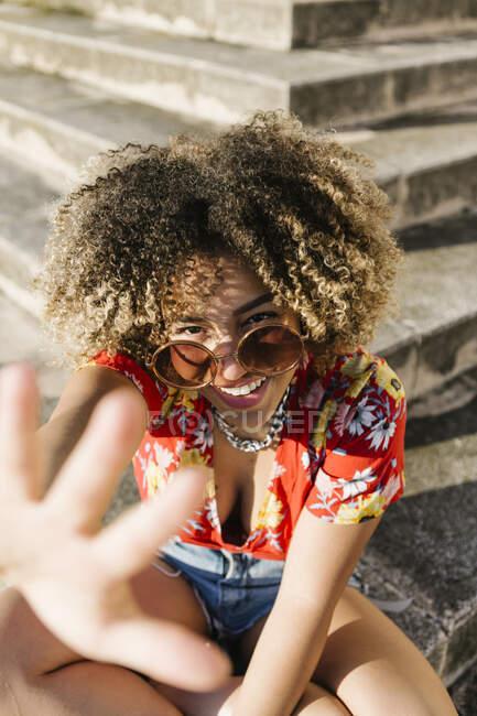 Mujer de moda mostrando gesto de parada mientras se sienta en los pasos durante el día soleado - foto de stock