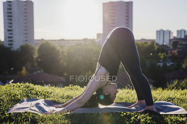Young woman performing yoga in downward facing dog position at city park — стоковое фото