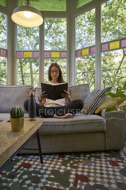 Жінка читає книжку, сидячи на дивані у вітальні. — стокове фото