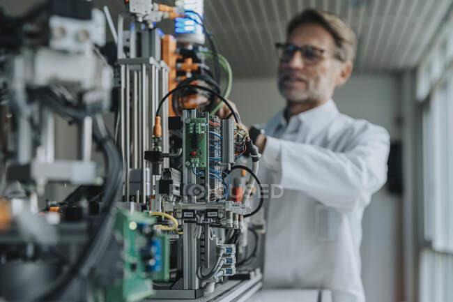 Науковець-чоловік винаходить машини в лабораторії. — стокове фото