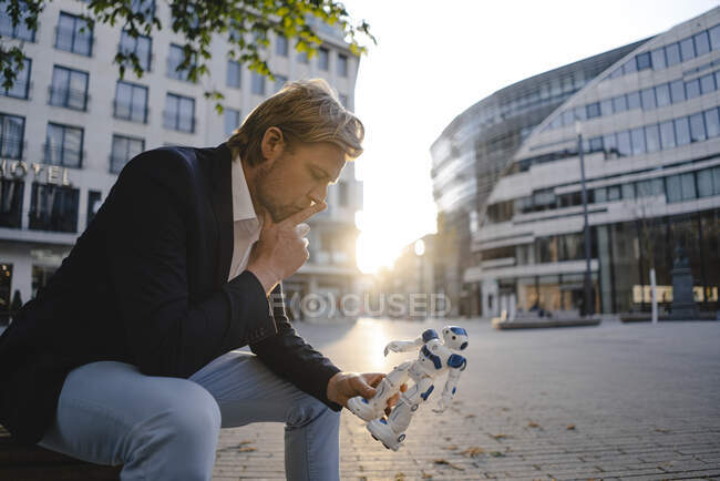 Businessman sitting on a bench in the city holding mini robot — Stock Photo