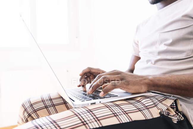 Joven hombre de negocios escribiendo en el ordenador portátil mientras está sentado y trabajando en casa - foto de stock