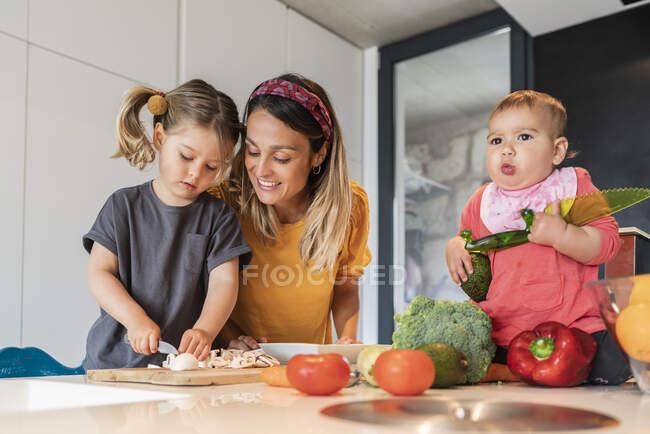 Menina bonito sentado na ilha, enquanto a mãe olhando para a filha cortar legumes em casa — Fotografia de Stock