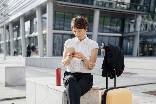 Female professional using smart phone while sitting on seat in city — Fotografia de Stock