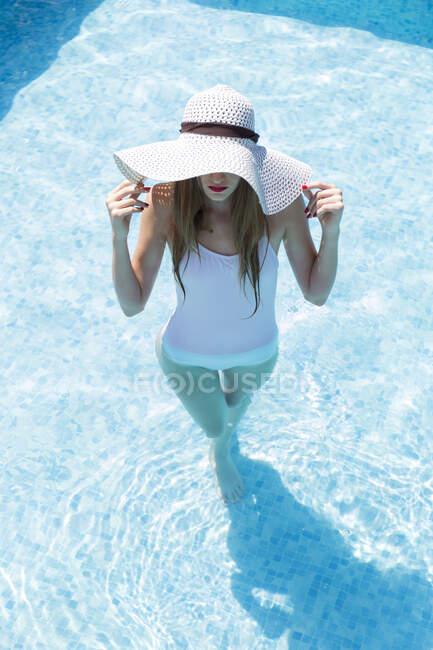 Giovane donna che indossa cappello nuotare in piscina in località turistica durante la giornata di sole — Foto stock