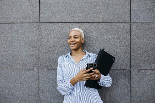 Mujer de negocios sonriente con carpeta y teléfono contra edificio en la ciudad - foto de stock