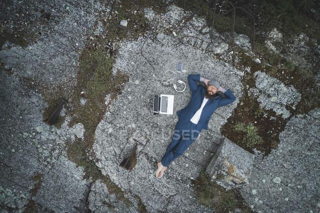 Vista aérea del hombre de negocios con traje con las manos detrás de la cabeza relajándose en la tierra en el bosque - foto de stock