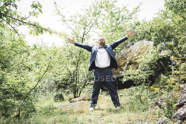 Empresário barbudo com braços estendidos exercitando-se em terra na floresta — Fotografia de Stock